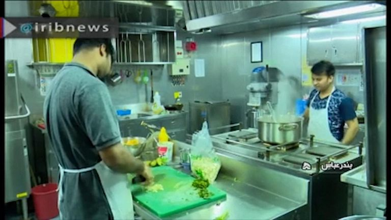 The crew of can be seen working in the kitchen