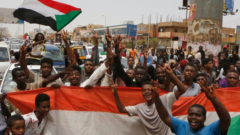Sudanese people celebrate in the streets of Khartoum after ruling generals and protest leaders announced they have reached an agreement on the disputed issue of a new governing body on July 5, 2019
