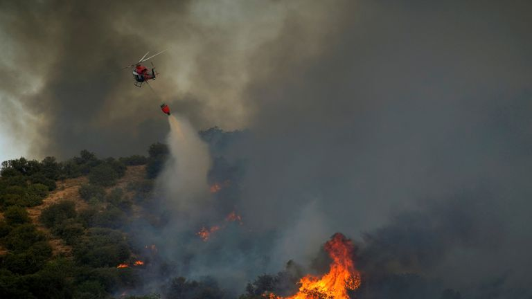 A helicopter drops water to distinguish a wildfire in Toledo in Spain