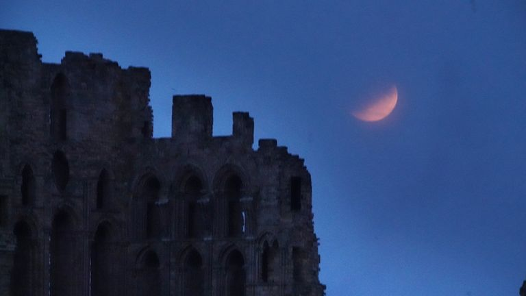 A partial lunar eclipse is visible above Tynemouth Priory, on the 50th anniversary of Apollo 11 launching on its moon mission