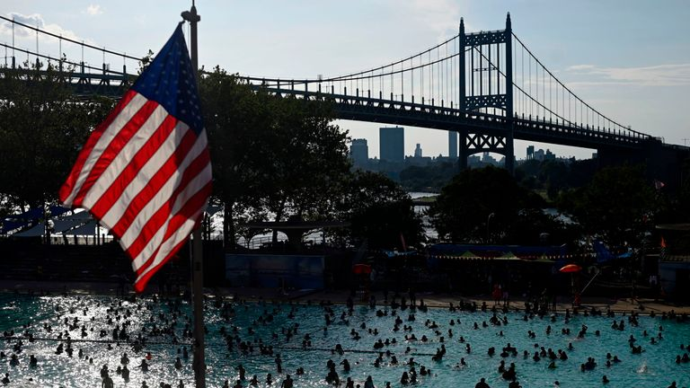 A US flag flies overhead as people enjoy the Astoria Pool on a hot afternoon in the borough of Queens, New York