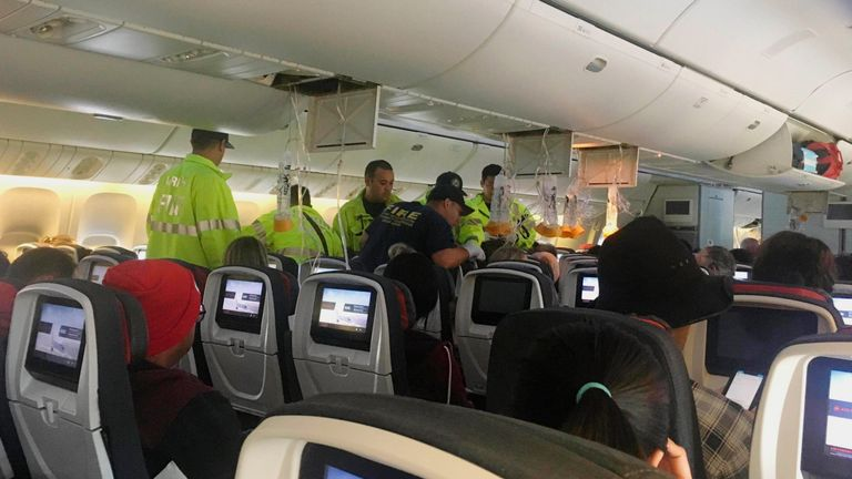 Responders treat a passenger on an Air Canada flight to Australia that was diverted and landed at Daniel K. Inouye International Airport in Honolulu