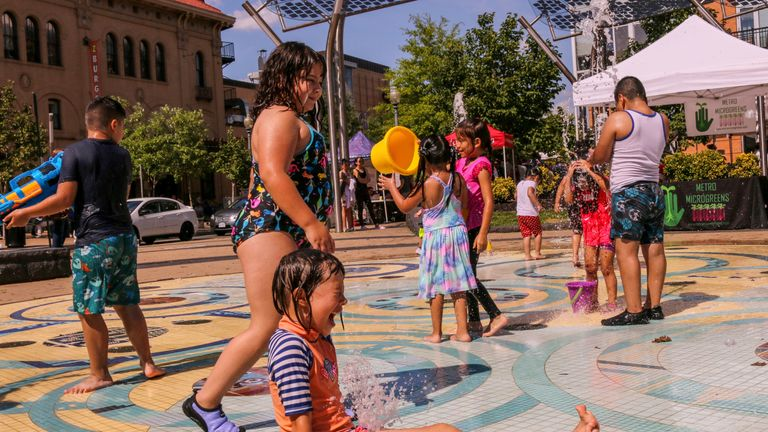 Children play at a fountain in the Columbia Heights neighbourhood of Washington DC