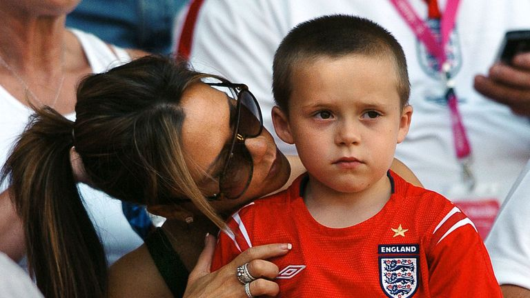 England's midfielder David Beckham's wife Victoria poses with their son Brooklyn, 17 June 2004 at Coimbra's stadium, before the Euro 2004 group B football match between England and Switzerland at the European Nations championship in Portugal