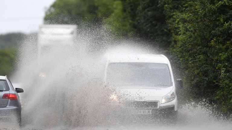 Cars make their way through standing water on the A47 near Peterborough