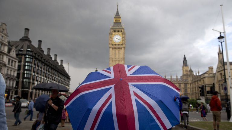 A pedestrian shelters from the rain beneath a Union flag themed umbrella as they walk near the Big Ben clock face and the Elizabeth Tower at the Houses of Parliament in central London on June 25, 2016, following the pro-Brexit result of the UK's EU referendum vote. The result of Britain's June 23 referendum vote to leave the European Union (EU) has pitted parents against children, cities against rural areas, north against south and university graduates against those with fewer qualifications. Lo