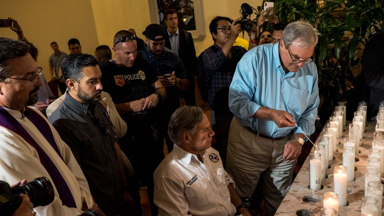 Texas Governor Greg Abbott (C) and El Paso Mayor Dee Margo (R) light candles after a vigil ceremony at Saint Pius X Church, following a deadly mass shooting, in El Paso, Texas, August 3, 2019. - A gunman armed with an assault rifle killed 20 people Saturday when he opened fire on shoppers at a packed Walmart store in Texas, the latest mass shooting in the United States. Texas authorities are investigating the Saturday mass shooting at a Walmart store in El Paso as a possible hate crime, the city's police chief said, as authorities study an online manifesto linked to the suspect. (Photo by Joel Angel JUAREZ / AFP)        (Photo credit should read JOEL ANGEL JUAREZ/AFP/Getty Images)
