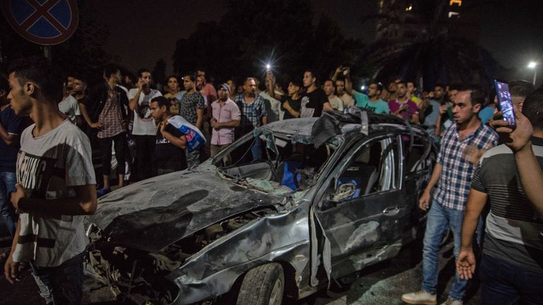 Onlookers gather around a charred car, following an accident just before midnight on August 4, 2019, outside the National Cancer Institute in the Egyptian capital Cairo. - At least 19 people have been killed and more than 30 injured when a speeding car driving against traffic crashed into three others causing a huge explosion in the capital, the Egyptian health ministry said today. (Photo by Aly FAHIM / AFP)        (Photo credit should read ALY FAHIM/AFP/Getty Images)