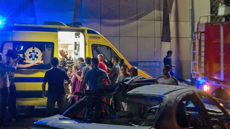 People gather near an ambulance during the night of August 5, 2019, at the scene of an accident that took place just before midnight on August 4, outside the National Cancer Institute in the Egyptian capital Cairo. - At least 19 people have been killed and more than 30 injured when a speeding car driving against traffic crashed into three others causing a huge explosion in the capital, the Egyptian health ministry said today. (Photo by Aly FAHIM / AFP)        (Photo credit should read ALY FAHIM/AFP/Getty Images)
