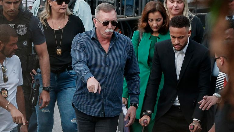 Brazilian football player Neymar (R) arrives on crutches at the Women's Defence Precinct in Sao Paulo, Brazil on June 13, 2019 to testify after Brazilian Najila Trindade filed a complaint against him on May 31, saying he assaulted her after inviting her to visit him in Paris. - Brazilian police said on Thursday they had filed a defamation suit against the woman who has accused football star Neymar of rape, after she insinuated the force was corrupt. (Photo by Ari FERREIRA / AFP)        (Photo credit should read ARI FERREIRA/AFP/Getty Images)
