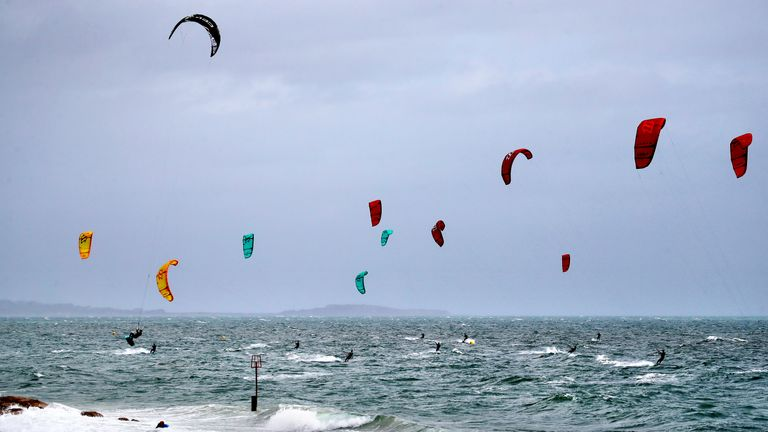 Kite surfers enjoy the strong winds off of Branksome Chine, near Poole in Dorset. Warnings for rain and wind came into force across nearly all of the UK today.