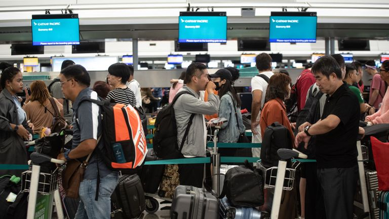 Passengers wait in line at check-in counters at Hong Kong's International Airport on August 14, 2019. - Flights were departing Hong Kong airport largely on schedule morning on August 14, a day after pro-democracy protesters caused chaos with a disruptive sit-in that paralysed the busy transport hub. (Photo by Philip FONG / AFP)        (Photo credit should read PHILIP FONG/AFP/Getty Images)