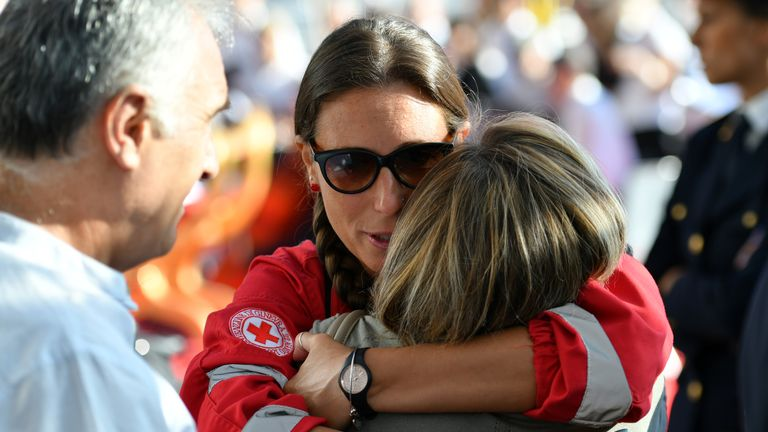 Red cross member embraces a relative before a mass for the first anniversary of the collapse of the Morandi bridge, on August 14, 2019 in Genoa. (Photo by Alberto PIZZOLI / AFP)        (Photo credit should read ALBERTO PIZZOLI/AFP/Getty Images)