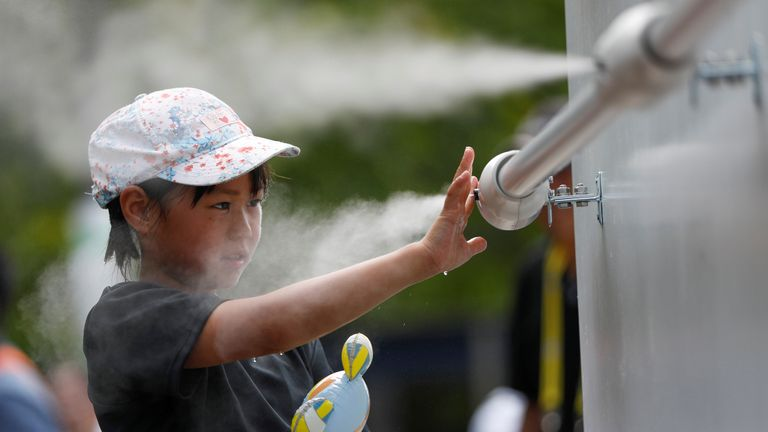 A visitor experiences a large-scale misting tower dispensing ultra-fine mist during a proving test of heat countermeasures for the Tokyo 2020 Olympic and Paralympic Games at the venue of FIVB Beach Volleyball World Tour, also acting as a test event for the games, in Tokyo, Japan July 25, 2019.     REUTERS/Issei Kato