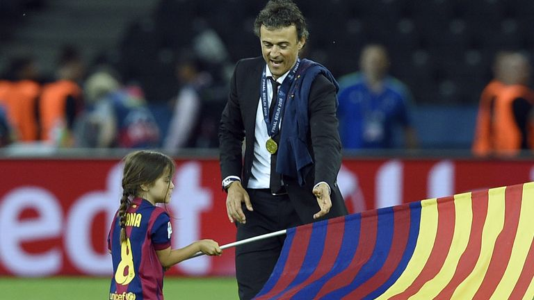 Barcelona's coach Luis Enrique and his daughter Xana wave a flag after the UEFA Champions League Final football match between Juventus and FC Barcelona at the Olympic Stadium in Berlin on June 6, 2015. FC Barcelona won the match 1-3.        AFP PHOTO / LLUIS GENE        (Photo credit should read LLUIS GENE/AFP/Getty Images)