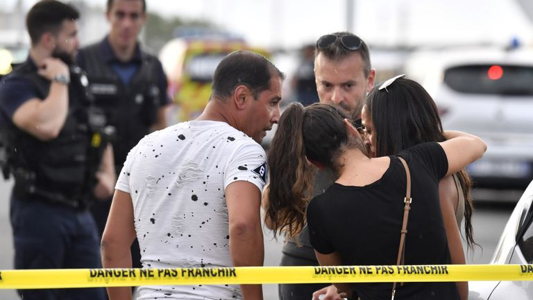 A witness (R) is comforted by friends in Villeurbanne on the outskirts of Lyon, south-eastern France on August 31, 2019, after a knife attack which has left one dead and six injured. - Two men, one armed with a knife and the other with a skewer, carried out the attack in Villeurbanne in southeastern France, the official said, without giving further details on the motive for the stabbing. (Photo by PHILIPPE DESMAZES / AFP)        (Photo credit should read PHILIPPE DESMAZES/AFP/Getty Images)
