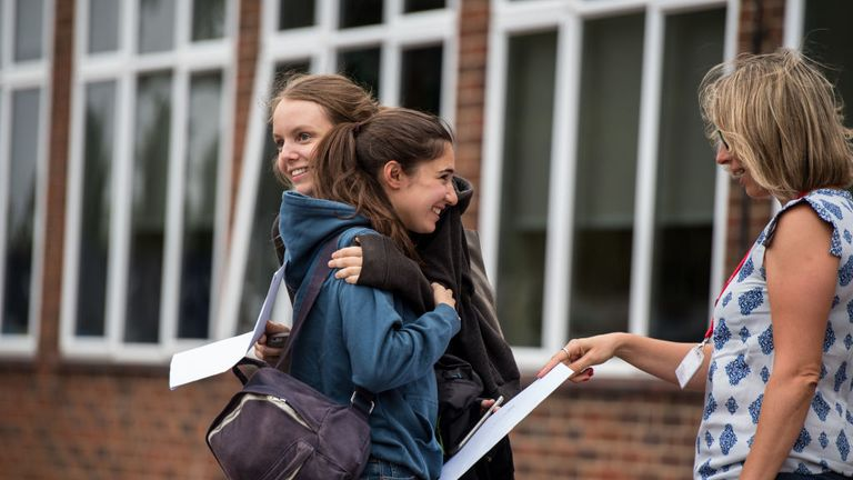 Students embrace each other after opening their A Level exam results in 2018