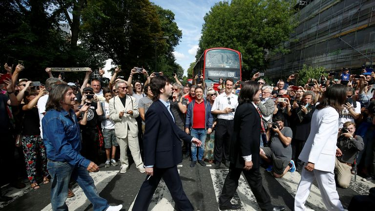Members of The Beatles cover band cross the zebra crossing on Abbey Road