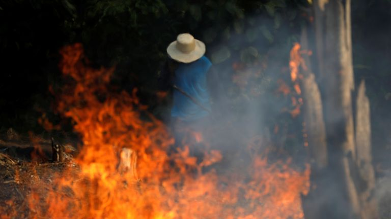A man works in a burning tract of Amazon jungle as it is being cleared by loggers and farmers in Iranduba, Amazonas state, Brazil