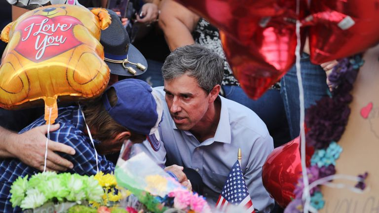 Democratic presidential candidate and former Rep. Beto O'Rourke (D-TX) (C) consoles a man at a makeshift memorial outside Walmart honoring victims of a mass shooting. The man is Antonio Basco, who lost his wife Margie