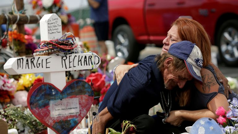 Antonio Basco, whose wife Margie Reckard was murdered during a shooting at a Walmart store, is comforted by a woman next to a white wooden cross bearing the name of his late wife, at a memorial for the victims of the shooting in El Paso, Texas, U.S. August 15, 2019. REUTERS/Jose Luis Gonzalez TPX IMAGES OF THE DAY
