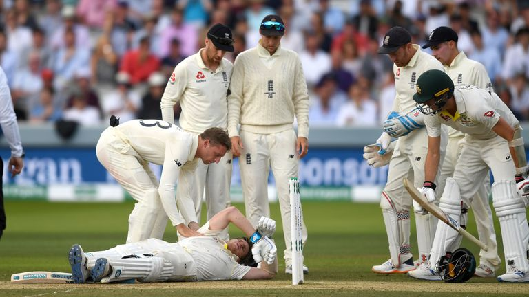 Jos Buttler, Jack Leech and Joe Root of England check on Steven Smith of Australia as he lies on the ground after been hit in the head by a ball from Jofra Archer of England during day four of the 2nd Specsavers Ashes Test match at Lord's Cricket Ground on August 17, 2019 in London, England