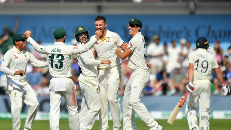 Australia's players celebrate the dismissal of England's Chris Woakes (R)