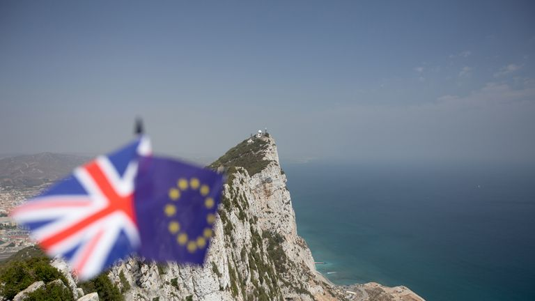 The Union Jack and the Flag of The European Union with The Rock of Gibraltar in the background, indicating the dispute over its sovereignty and the effects of Brexit with plenty of copyspace