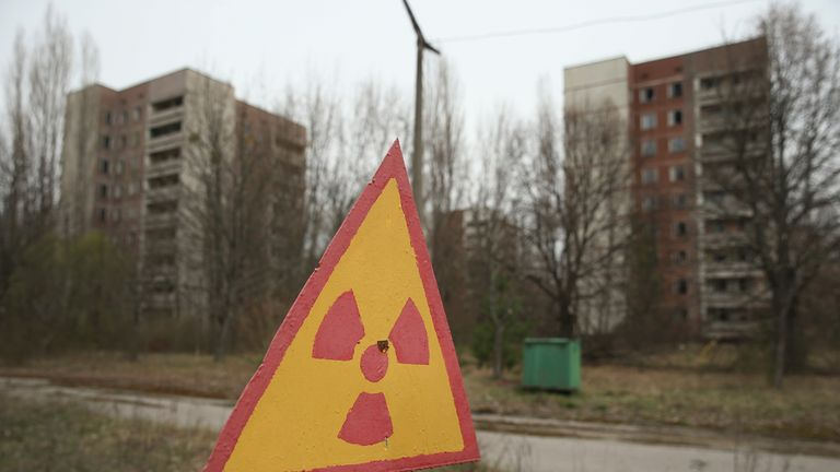 A sign warns of radiation contamination near former apartment buildings, which stand abandoned inside the exclusion zone in Pripyat, Ukraine
