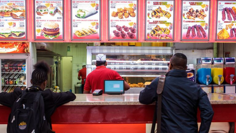 Customers wait at the counter of a chicken shop in Camberwell on April 26, 2018 in London, England