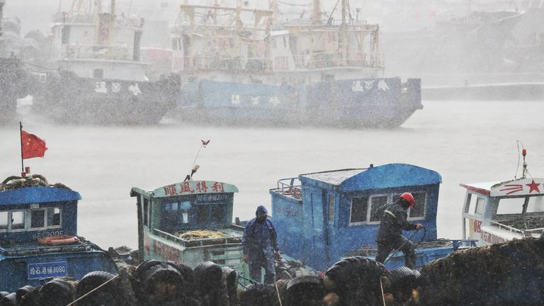 Fishermen secure boats at a port in Taizhou, China's eastern Zhejiang province, ahead of the arrival of Typhoon Lekima