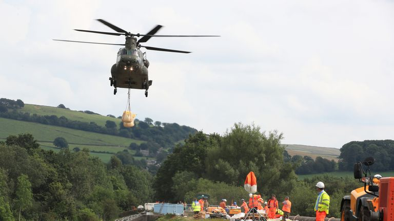 An RAF Chinook helicopter flies in sandbags to help repair the dam at Toddbrook reservoir near the village of Whaley Bridge in Derbyshire