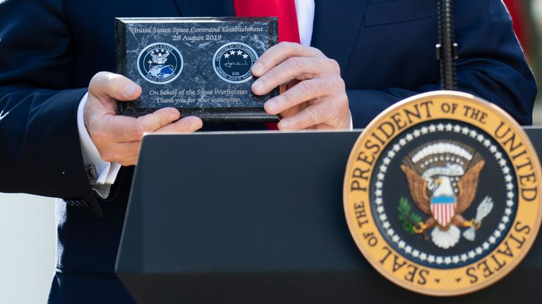 The president shows off a commemorative plaque