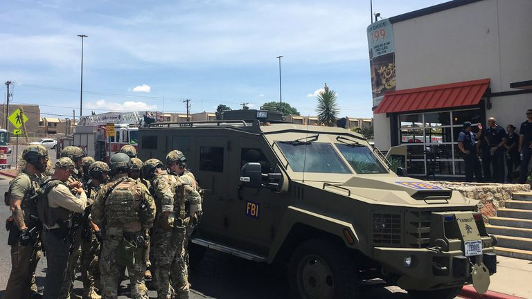Armed Policemen gather next to an FBI armoured vehicle next to the Cielo Vista Mall as an active shooter situation is going inside the Mall in El Paso on August 03, 2019