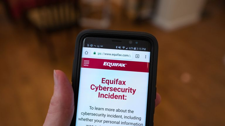 "Close-up of the hand of a man holding a mobile phone open to the web site of credit bureau Equifax, with text on the website reading ""Equifax Cybersecurity Incident"", providing steps for consumers to take following a security breach at the company, San Ramon, California, September 28, 2017. (Photo by Smith Collection/Gado/Getty Images)"