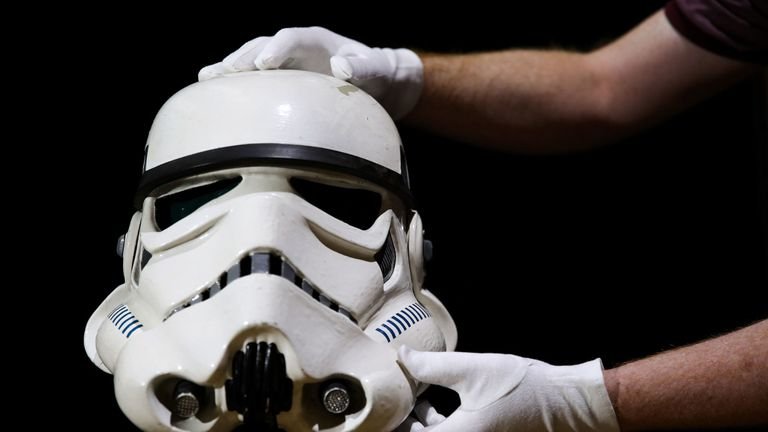 A prop store employee adjusts a screen matched Tantive IV Stormtrooper helmet from 1977 film Star Wars: A New Hope