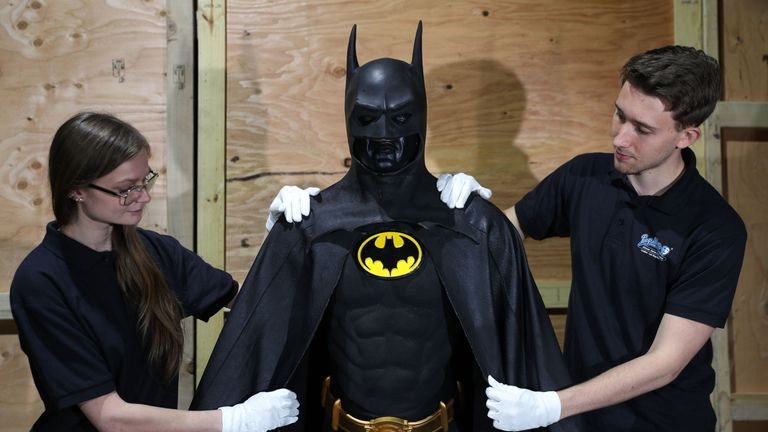 Prop store employees adjust the Batman batsuit, worn by Michael Keaton in the 1989 film Batman