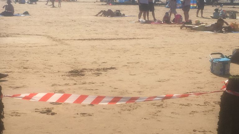 A warning tape is set at the beach in Frinton, Essex, as emergency services received several reports of people coughing and struggling to breathe