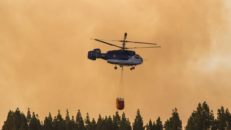 Helicopters carry water to dump on the fire near Valleseco