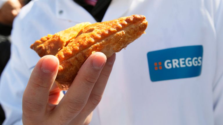 A Greggs employee holds one the chain's tradition non-vegan products