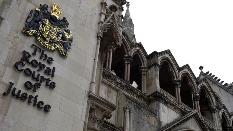 The Royal Coat of Arms and signage is pictured on an external wall of The Royal Courts of Justice on The Strand in central London on August 21, 2016.