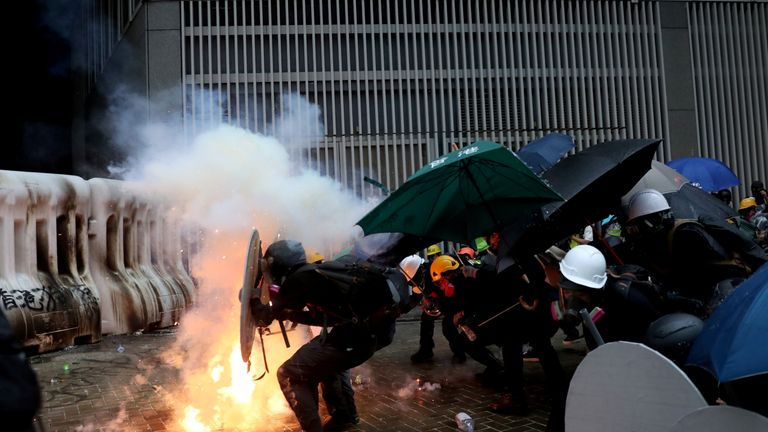 Demonstrators take cover during a protest in Hong Kong, China on Saturday