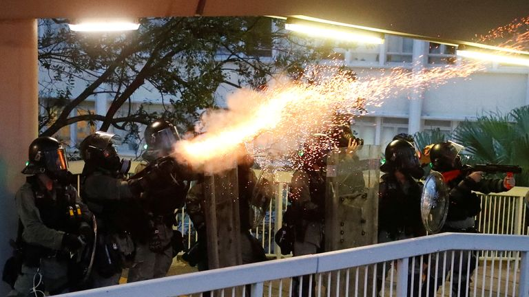 Police officers fire tear gas at demonstrators during a protest in Hong Kong, China on Saturday