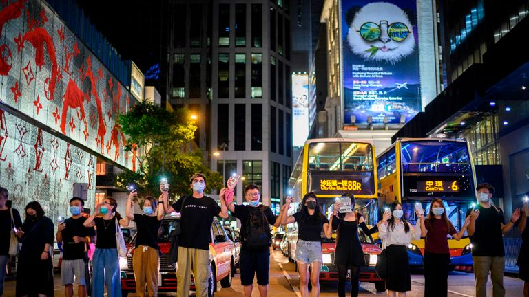 People hold hands and use their phone torches as they form a human chain along a pedestrian crossing in Hong Kong on August 23, 2019