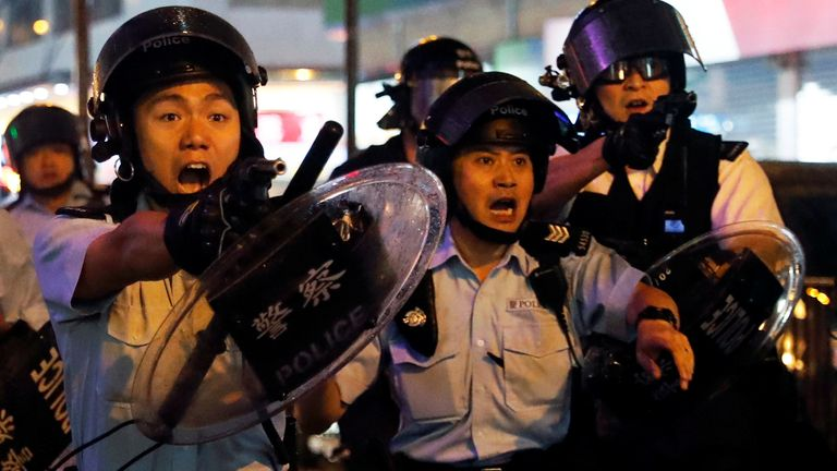 Hong Kong police point handguns at protesters.