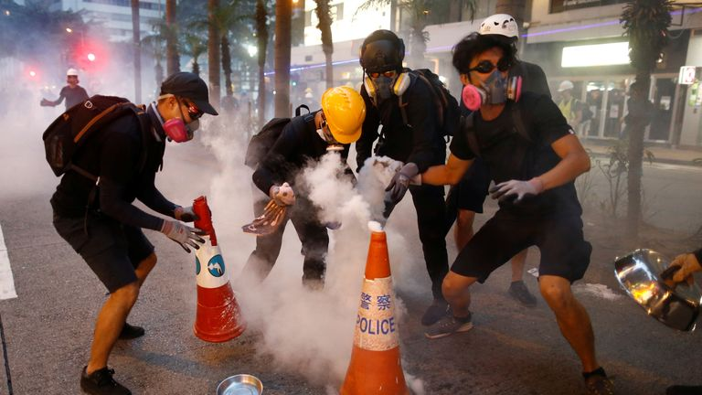 Protesters try to extinguish tear gas canisters in Wan Chai neighbourhood on Sunday