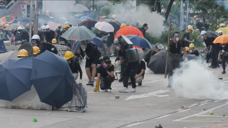 Protesters move behind umbrellas as tear gas flies on the streets of Hong Kong