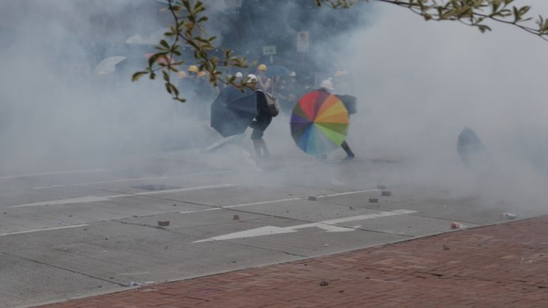 Protesters push through the tear gas