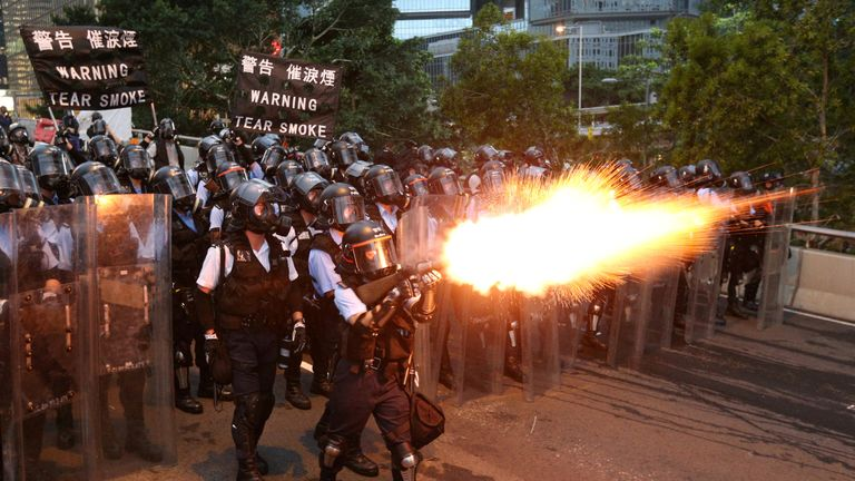 Police officers fire tear gas during a demonstration on 12 June