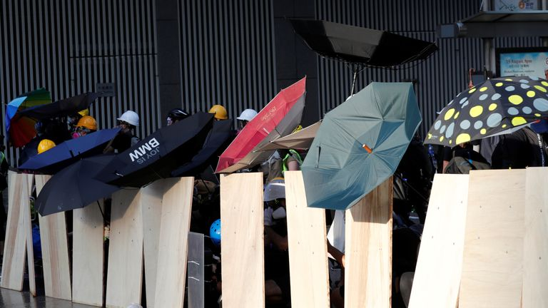 Protesters use umbrellas as they form a barricade